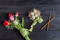 Eggs, a bouquet of tulips and church candles. The easter composition. Eggs, a bouquet of tulips and church candles on wooden table close-up Stock Image
