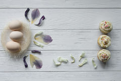 Easter composition with eggs and dried violet petals of flowers Stock Photography