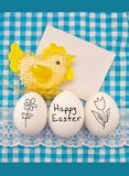Easter composition with eggs and handmade toy chicken on a cloth in blue-white cell Stock Photo