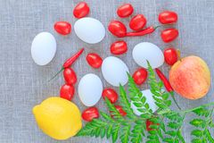Organic food composition: eggs, tomatoes, chilli pepper, apple and lem stock photo