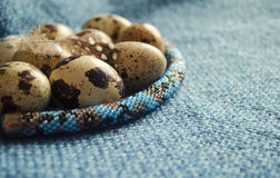 Easter composition with feather, quail eggs and beaded jewellery on woolen fabric. Stock Photos
