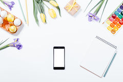 Easter composition: flowers, mobile phone, painted eggs, waterco Stock Photos