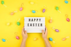 Easter composition, greeting card with child hand, lightbox text Happy Easter, colored decorative eggs on color background. Chocolate table kid coral minimal royalty free stock photography