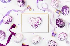 Easter composition with heart, painted eggs, sequins and silk ribbons on a white background. Space for a greeting text royalty free stock photography