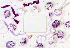 Easter composition with lilac marble eggs, sequins and silk ribbons on a white background. Space for a greeting text. Easter, spring concept, template cards Royalty Free Stock Photo
