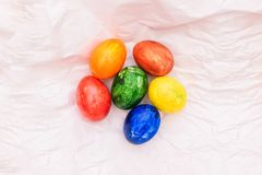 Easter composition with natural eggs on a white background. On crumpled paper are colorful eggs. Easter holiday royalty free stock photo