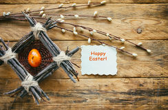 Easter composition, nest of twigs, quail orange egg Royalty Free Stock Photos