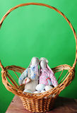 Easter composition. Soft toys of rabbits handmade with eggs in a wicker basket. Detail of decor. Green background Royalty Free Stock Photography