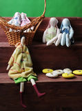 Easter composition. Soft toys of rabbits handmade with eggs in a wicker basket. Detail of decor. Green background Royalty Free Stock Photo