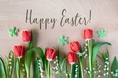 Easter composition with with spring flowers, tulips and lily of. The valley on wood. Text `Happy Easter` embossed on the wood Royalty Free Stock Photos