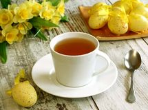 Easter composition of tea cup, eggs and flowers on Royalty Free Stock Photos