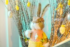 Easter composition with toy rabbit and eggs hanging on pussy-willow bouquet on the blue background stock photo