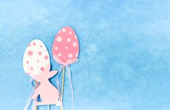 Easter composition with traditional decor. Small decorative colorful eggs and soft feathers. Easter composition with traditional decor. Wooden decorative rabbit royalty free stock photos
