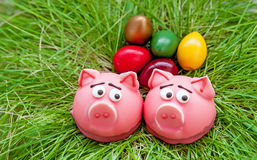Easter composition of two baked sweet pig in a pink frosting in the nest of green grass with colored eggs Stock Photo