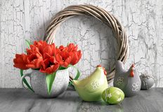 Easter composition with wooden wreath, red tulips, ceramic hens. Easter decorations on gray rustic background. Arrangement with wooden wreath, red tulips Stock Photography
