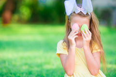 Easter concept. Adorable little girl wearing bunny ears with Easter eggs on spring day Stock Images