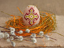 Easter concept. Beaded egg and willow twig Stock Photos