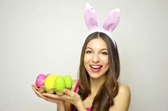 Easter concept. Beautiful young woman with bunny ears holdings egg carton of colorful Easter eggs on white background. Copy space. Easter concept. Beautiful Royalty Free Stock Image