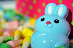 Easter Concept. Blue Easter Bunny surrounded by colorful Easter candy Stock Images