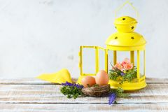 Easter concept. Bright spring flowers with Easter eggs near a yellow decorative lantern stock photography