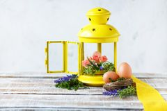 Easter concept. Bright spring flowers with Easter eggs near a yellow decorative lantern royalty free stock photos