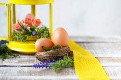 Easter concept. Bright spring flowers with Easter eggs near a yellow decorative lantern royalty free stock photo