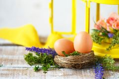 Easter concept. Bright spring flowers, a nest with Easter eggs next to a yellow lantern on a light background stock image
