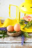 Easter concept. Bright spring flowers, a nest with Easter eggs next to a yellow lantern on a light background royalty free stock images
