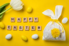 Easter concept - bunny shaped bag with eggs and flowers on bright yellow background,. Top view royalty free stock photo
