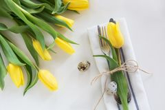 Easter concept with copy space. Decorative easter place setting with yellow tulip, a quail egg on a white. Easter concept with copy space. Decorative easter Stock Image