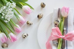 Easter concept with copy space for your Happy Easter wishes. Decorative easter place setting with pink tulip, a quail egg on a whi. Te background Stock Photos