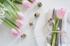 Easter concept with copy space for your Happy Easter wishes. Decorative easter place setting with pink tulip, a quail egg on a whi. Te background Royalty Free Stock Photography
