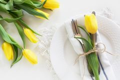 Easter concept with copy space for your Happy Easter wishes. Decorative easter place setting with yellow tulip, a quail egg on a w. Hite background Stock Images