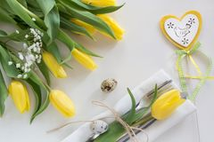 Easter concept with copy space for your Happy Easter wishes. Decorative easter place setting with yellow tulip, a quail egg on a w. Hite background Royalty Free Stock Image