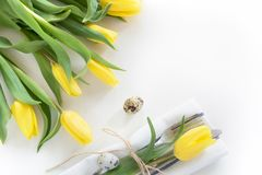 Easter concept with copy space for your Happy Easter wishes. Decorative easter place setting with yellow tulip, a quail egg on a w. Hite background Royalty Free Stock Photography