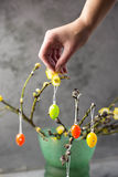 Easter concept. Girl holding colored eggs. Willow branches. Stock Photos