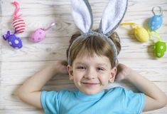 Easter concept. Happy cute child wearing bunny ears getting ready for Easter stock image