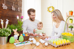 Easter concept. Happy mother and father preparing home decoration with their child for Easter holidays Royalty Free Stock Photos
