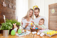 Easter concept. Happy mother and father preparing home decoration with their child for Easter holidays Royalty Free Stock Image