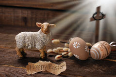 Easter concept with lamb and cross symbol. Easter concept with cross in light rays and lamb as a symbol of  sacrifice offered to God Stock Images