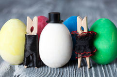 Easter concept postcard. Clothespin man, woman and colorful easter eggs Royalty Free Stock Images