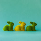 Easter concept. Three rabbits on the turquoise background. Royalty Free Stock Photo
