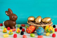 Easret concept picture with gold Easter eggs in basket next to chocolate Easter bunny and baby chicken with candy on blue wooden b stock images