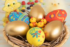 Symbolic Easter attributes eggs in a basket with yellow baby chicken, rabbit and sweets Easter concept stock photography