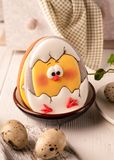Easter cookie with painted hatched chicken in bowl near quail eggs and green napkin stock image