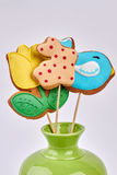 Easter cookies in vase isolated. Frosted biscuits on sticks Stock Photos
