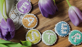 Easter cookies words alphabet wood background message tulips flowers Stock Photos