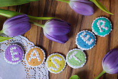 Easter cookies words alphabet wood background message tulips flowers Stock Images