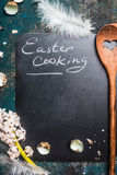 Easter cooking text on black blank chalkboard with wooden spoon, shell of egg and flowers Stock Photography