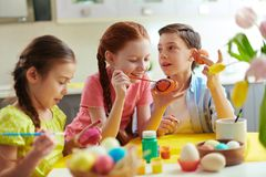 Easter craft. Photo of cute kids painting Easter eggs at home stock photos